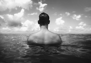 Black and white image of man swimming in ocean