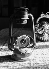 B & W Still life of antique kerosene lamp and ceramics with crocheted cloth