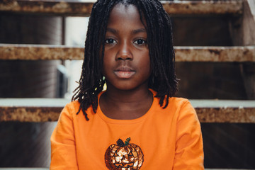 African American girl sitting on stairs in an alley