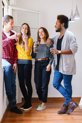 Group of young friends having fun and drinking red wine at home.