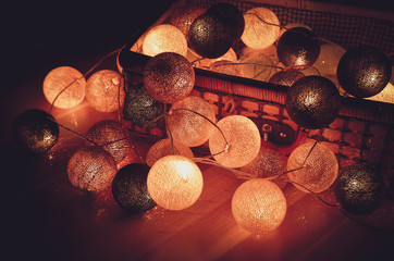 New Year and Christmas cotton light balls garland shining in the dark in a vintage basket.