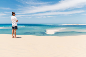 Young man overlooking the ocean from the top of a sand dune on a tropical island