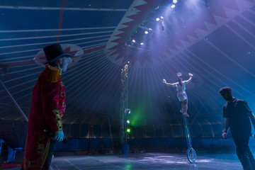 Circus performer on unicycle on stage with ring master and stage hand