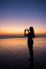 Silhouette of girl taking picture on phone