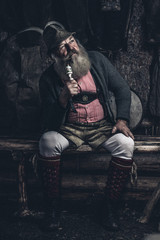 old full bearded man in lederhosen sitting inside a wooden cabin smoking a pipe