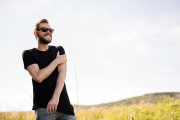 Handsome man wearing a black tshirt and jeans with dark sunglasses, standing alone on an empty field on a sunny summer day.