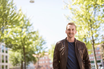 Trendy blonde man standing outdoors in a city, with trees around him wearing a brown leather jacket smiling towards camera.