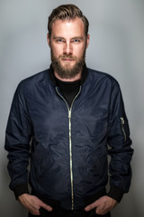 Tough man in beard wearing a blue jacket standing against a grey background staring at camera.