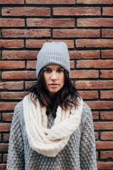 Portrait of girl with winter clothes on brick wall.