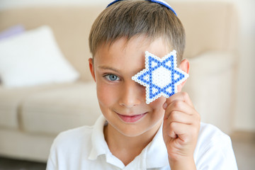 Boy holding Star of David at home