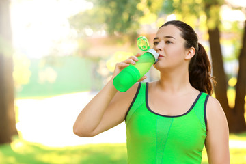 Overweight young woman in sportswear drinking water outdoors. Weight loss concept
