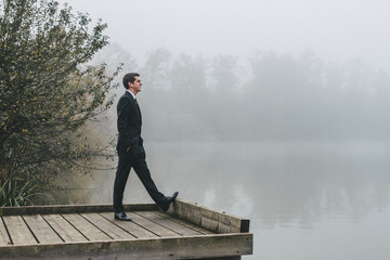 groom standing on a jetty looking at the lake