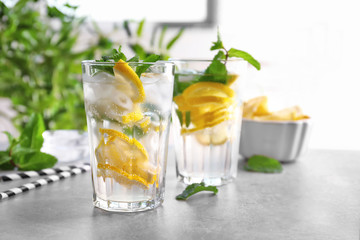 Glasses of cocktail with mint and lemon on table