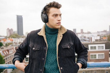 Young man listening to music and looking to his side.