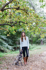 Fashionable woman standing with her dog on a leash in a park