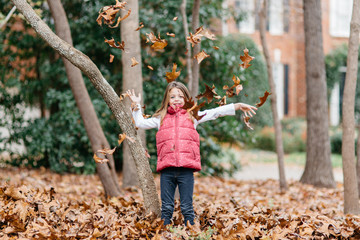 Cute girl throwing leaves around her outside