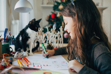Girl and Her Kitten Writing a Letter to Santa