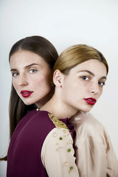 Two beautiful women with freckles and red lipstick looking in camera in studio