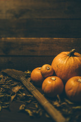Bunch of pumpkins and broom on wooden background
