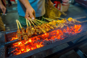 JAKARTA, INDONESIA: Street barbecue with meat skewers sizzling, very hot fire burning and man preparing food