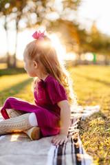 A little girl sitting on a picnic blanket, basking in the sunlight.