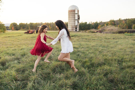 Two friends  hold hands and dance in field
