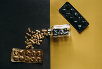 Golden pills on black background coming out of a bottle that contains black pills on gold background