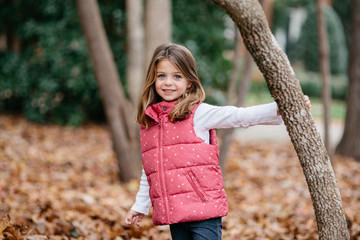 Cute young girl in a vest standing outside holding a tree