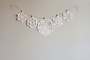 Paper snowflake cutouts hanging from string on wall