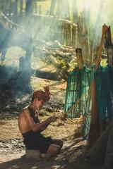 Asian fisherman make wicker fishing equipment at countryside.