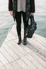 Young woman with winter clothes and black handbag standing on the dock.