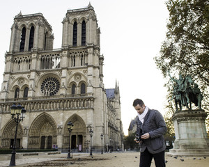 Tourist Photographing Notre Dame de Paris with Vintage Medium Format Film Camera