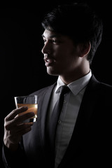 portrait of Asian man in black formal suit with a glass of whisky