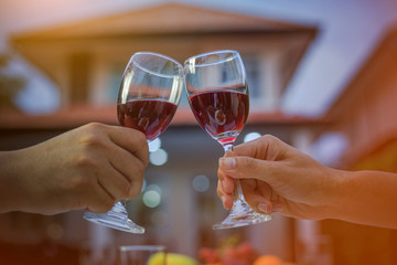 Man hand and woman hand holding a glass of red wine to celebrate Christmas and New Year. The back of the house is a bokeh of light. In the evening when entering the winter.
