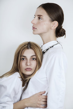 Two beautiful women in white with freckles and red lipstick looking in camera in studio