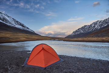 An orange tent near a river in the Mountains