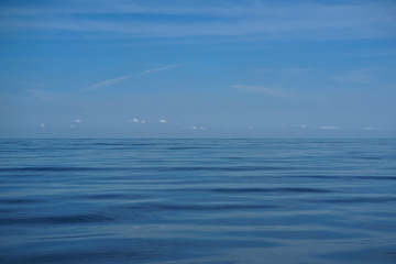 Natural background scene of bright blue sky horizon and white cloud above deep blue sea water ripple freezing motion