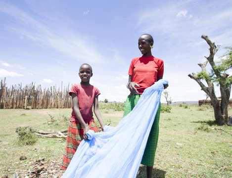 Mother and Daughter preparing mosquito net for daughter's sleeping area.