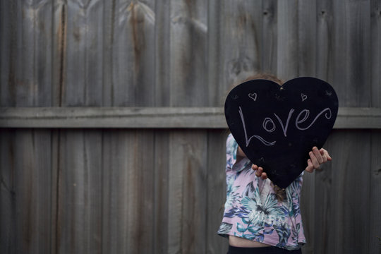 Girl holding her love chalkboard heart against the wall