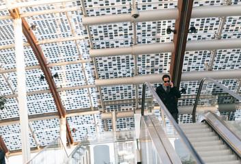 Young businessman on escalators