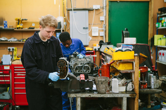 Two apprentice mechanics working on repairing an engine in a workshop