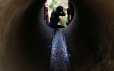 Santos washes her hair with mountain spring water coming through a pipe, after the island was hit by Hurricane Maria in September, in Toa Alta
