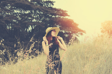 Female tourist wearing a hat standing on an outdoor lawn. She breathes fresh air for her vacations. happy holiday