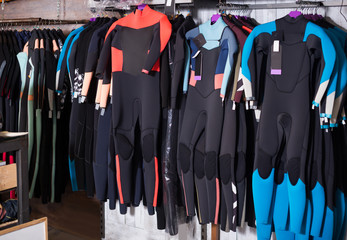 Image of colorful wetsuit hanging in the shop for surfing