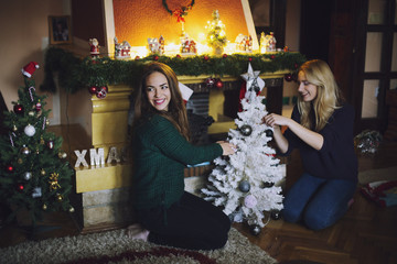 Two female friends preparing Christmas tree