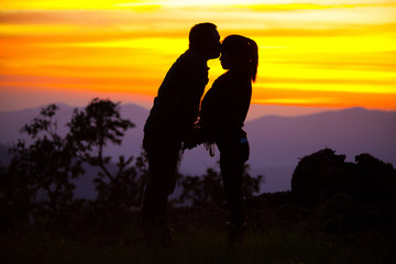 Loving couple showing heart symbol on hands,twilight background