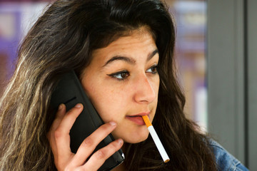 Jeune femme en train de fumer et téléphoner