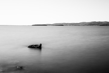 Long exposure view of a rock in the middle of a lake, with satin water