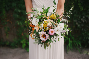 Bride holding simple organic and earthy garden flower wedding bouquet