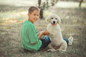 Retriever pup Lovely scene handsom teen boy enjoying summer time vacation with best friend dog ivory white labrador puppy.Happy airily careless childhood life in world of dreams